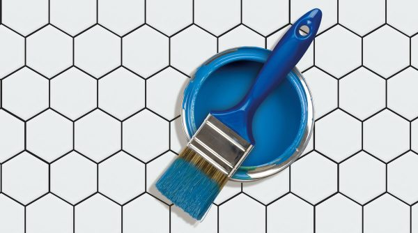 a blue paint brush and paint on hexagonal ceramic tiles