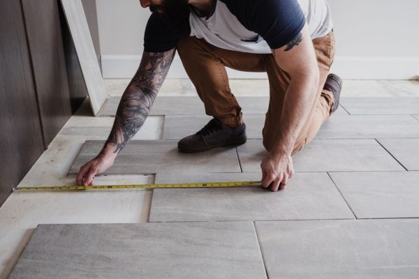 a man measuring floor tiles with a measuring tape