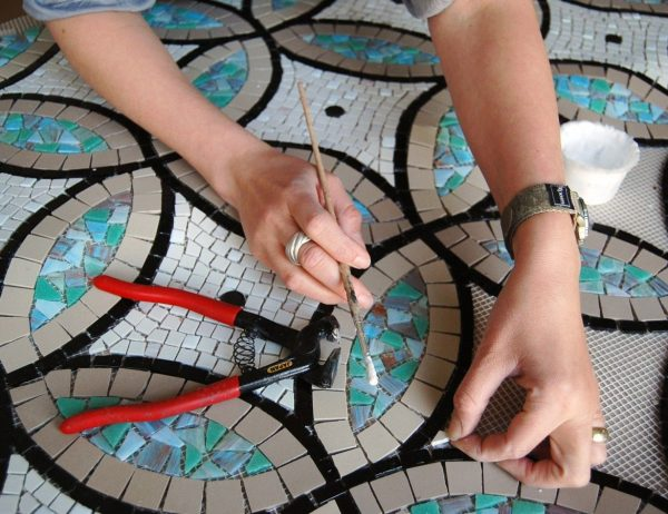 a woman putting glue on small mosaic pieces before putting it in place