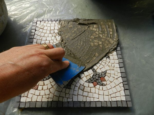 a man putting cement on tiles