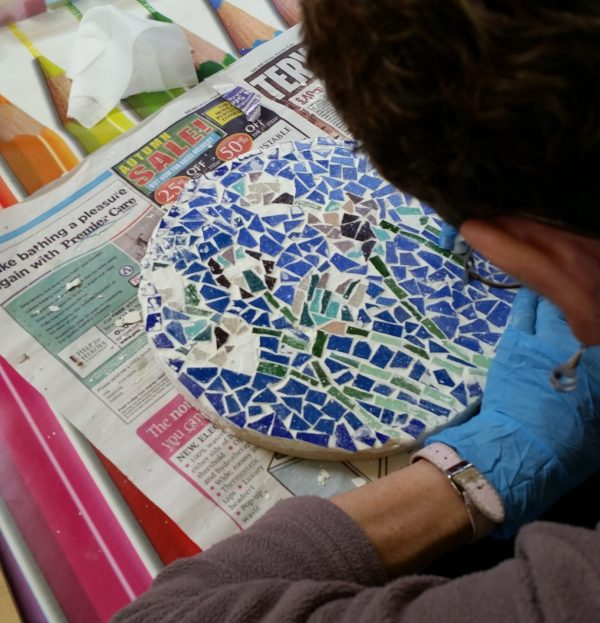 a man carefully crafting mosaic out of broken blue tiles