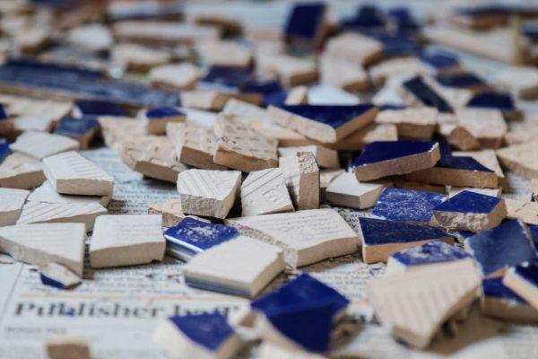 shattered blue tiles on a newspaper