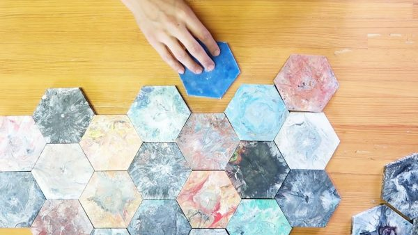 a person putting together hexagonal tiles