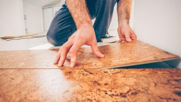 A handyman installing floor tiles