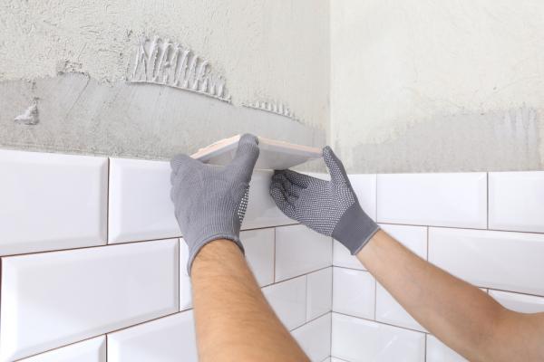A person repairing bathroom tiles